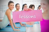 Fit blonde holding card saying lessons against against yoga class in gym