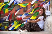Young girl sitting on Buddhist stupa, prayer flags flying in background.