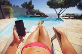 stock photo of sunbathing  - Young lady wearing bikini using mobile phone while sunbathing by the pool - JPG