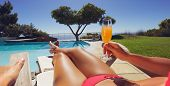 stock photo of pov  - Young lady in bikini holding orange juice glass while sitting on a lounge chair along the poolside on a sunny day - JPG