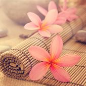 Health spa setting, low light with ambient. Frangipani, hot and cold stone on bamboo mat in vintage
