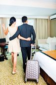Rear view of couple arriving to hotel room