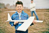 Photo of happy kid with toy airplane looking at camera with his father on background