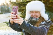 Portrait of teenage girl taking selfie picture with mobile phone outside in winter