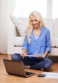 tax, finances, technology, home and happiness concept - smiling young woman with papers, laptop comp