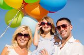 summer holidays, celebration, children and people concept - happy family with colorful balloons outd