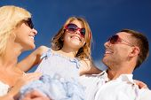 summer holidays, family, child and people concept - happy family in sunglasses over blue sky