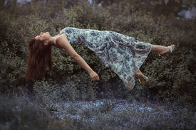 stock photo of sweet dreams  - Levitation girl on a bed in a sweet dream - JPG