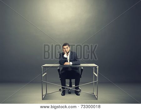 tired businessman sitting at table and looking at camera. photo in the dark room with empty copyspace