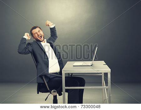 tired businessman yawning and stretching oneself. photo in the dark room