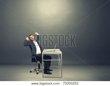 fatigued businessman yawning and stretching oneself. photo in the dark room