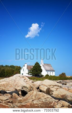 A small white cloud hangs over the white Chapel of Port au Persil, Saint-Simeon, Quebec, Canada.