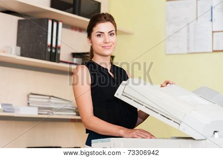 Pretty young secretary using a copy machine