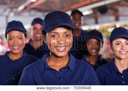 happy young african factory worker with colleagues