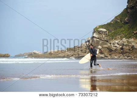 surfer in wetsuit carrying a surfboard runs along the sea with beautiful reflection in water
