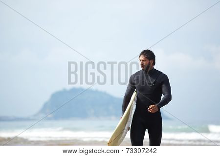 Handsome young surfer man walking at ocean beach holding his surfing board