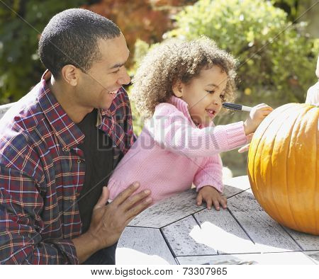 African father and daughter decorating pumpkin