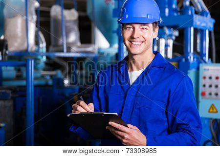 male industrial technician working inside a factory