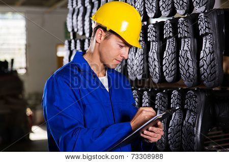 gumboot factory worker checking inventory in stockroom
