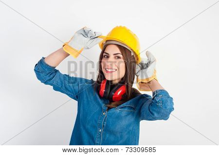 Young woman wearing a yellow hard hat and full protective gear smiling at the camera.