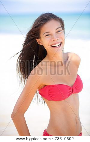 Bikini beach asian caucasian woman smiling happy on travel vacation holidays by blue ocean sea at tropical resort. Cheerful smiling excited mixed race girl laughing full of joy looking at camera.