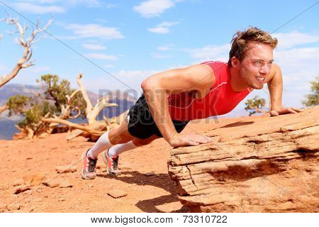 Fitness athlete man training push ups in amazing nature landscape. Strength training fit male working out exercising outdoors in summer doing incline push-up.