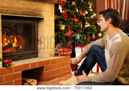 Man with cup of hot drink near fireplace in Christmas decorated house
