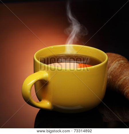 hot tea in cup and croissant