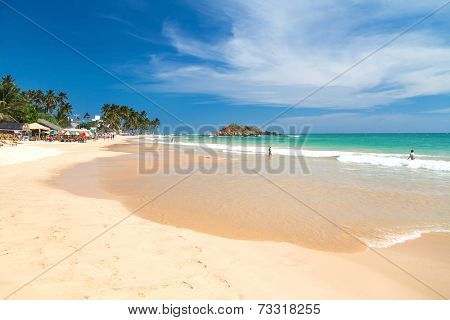 WELIGAMA, SRI LANKA - MARCH 5, 2014: Tourists on beautiful sandy beach. Tourism and fishing are two main business in this town.