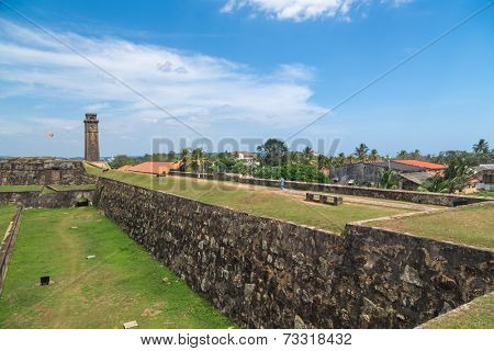 GALLE, SRI LANKA - MARCH 9, 2014: Walls of Galle fort with clock tower in distance.  Fort was originally built in 1684 to house the Dutch Governor and his staff and today is UNESCO World Heritage Site