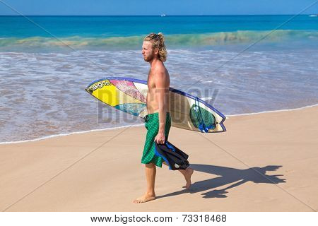 UNAWATUNA, SRI LANKA - MARCH 6, 2014: Young man  walks on sandy beach carrying surf board. Unawatuna is well known tourist international destination for board surfing.