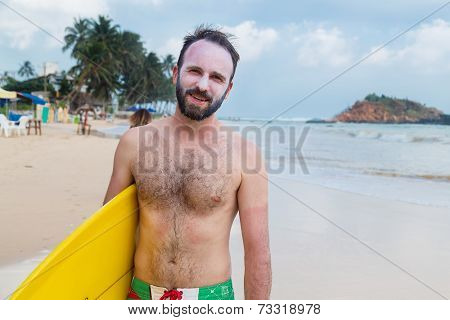 UNAWATUNA, SRI LANKA - MARCH 6, 2014: Young man wearing sunblock on his face stands on sandy beach holding the surf board. Unawatuna is well known tourist international destination for board surfing.