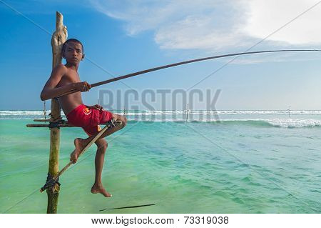 UNAWATUNA, SRI LANKA - MARCH 9, 2014: Young stilt fisherman at Hikkaduwa Beach. Most real stilt fishermen have been long gone. Today it's mainly young boys posing as stilt fishermen for tourists.