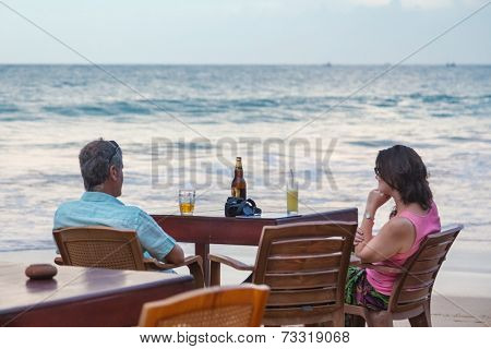 UNAWATUNA, SRI LANKA - MARCH 6, 2014: Tourist  couple having drink at beach bar. Unawatuna is a major tourist attraction in Sri Lanka  famous for its beautiful beach and corals.