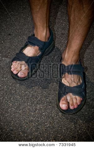 A Man's Feet In Sandals.