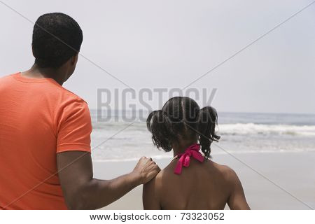 African father and daughter looking at ocean