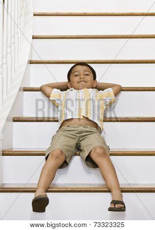 Hispanic boy laying on stairs