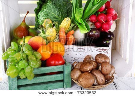 Vegetables in wooden boxes on white wooden box background
