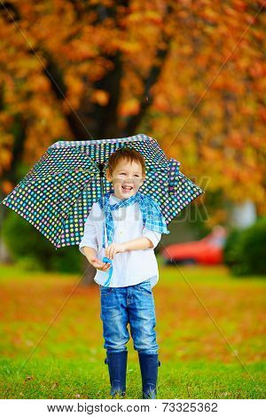 Happy Boy Walking Under An Autumn Rain