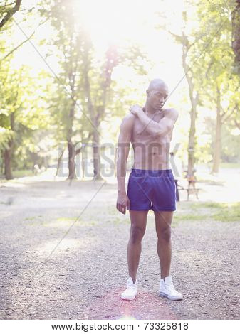 African man standing in park with bare chest