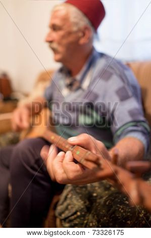 Elderly man with mustache playing old type guitar