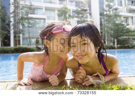 Asian sisters getting out of swimming pool