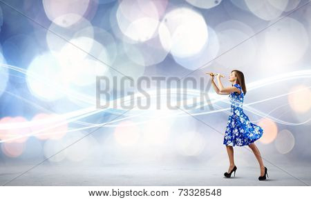 Young woman in blue dress playing fife against bokeh background