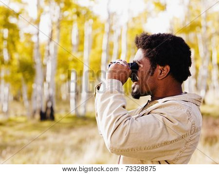 African man looking through binoculars