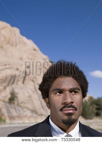African businessman in front of mountain