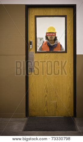 Asian warehouse worker looking through door