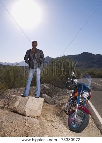 Hispanic woman standing next to motorcycle