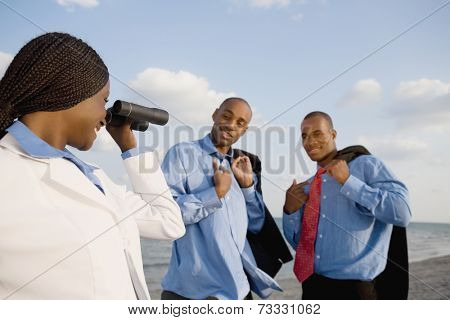 African businesswoman looking through binoculars at co-workers