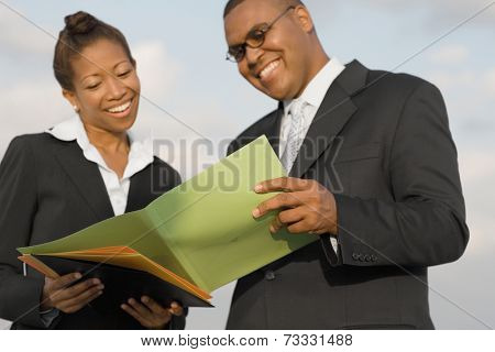 African businesspeople reading paperwork