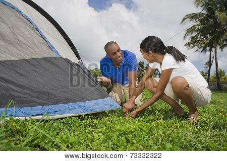 Multi-ethnic couple setting up tent